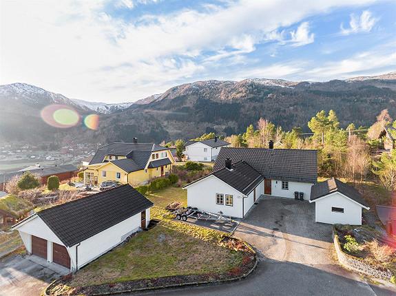 Sørvestvendt einebustad med tilnærma flat tomt, utleigeleilegheit og stor garasje