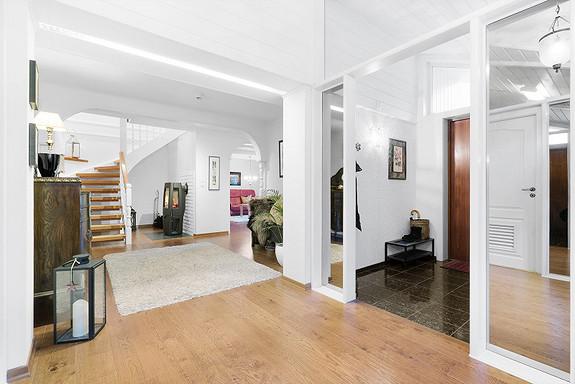 Flott og lys entré! Peisovn under trappen gir god varme i store deler av huset.