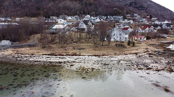 Friluftsområde ved sjøen med bålpanne, grill og benker