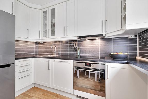 Pent og praktisk kjøkken, takhøye skap som utnytter den gode takhøyden i leiligheten
