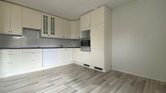 Pent kjøkken inkludert hvitevarer som stekeovn, platetopp, kjøleskap og frys.